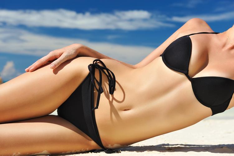 woman posing showing abdomen on beach