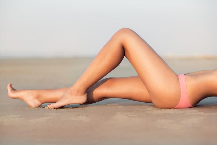 womans lower body posing on beach